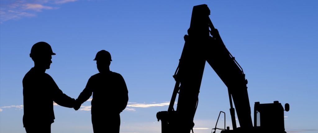 A royalty free image from the construction industry of two workers shaking hands.